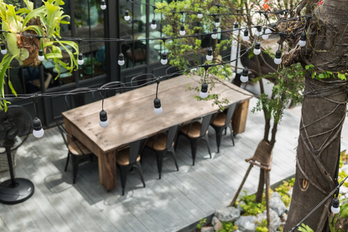 Timber Decking with Dining table in backyard garden Focus on bulb